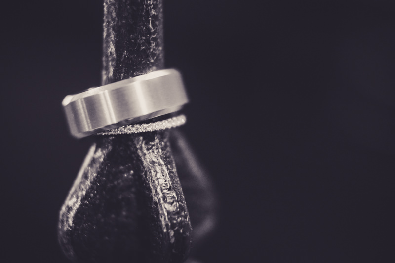 black and white image of wedding rings on an iron spike