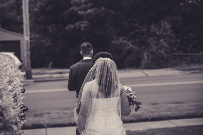 black and white image of the bride walking to the groom during the first look