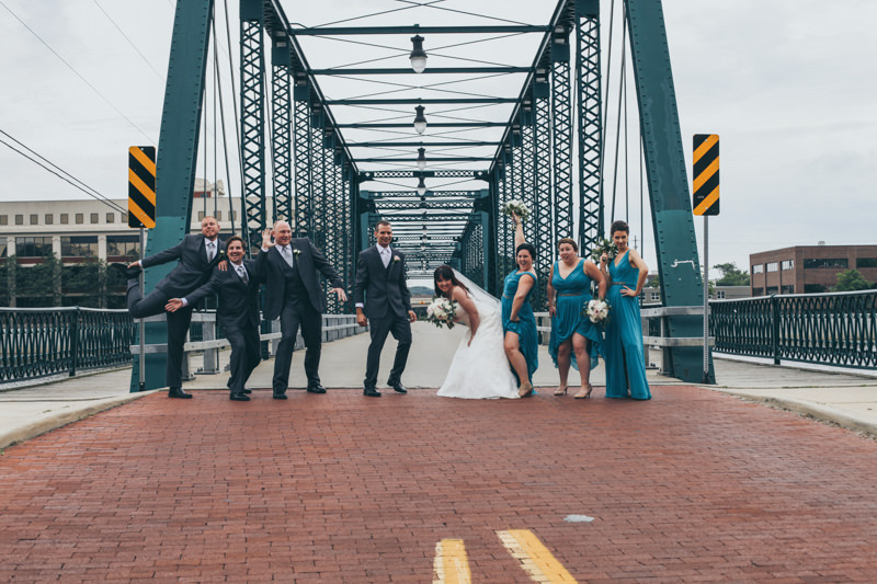 bridal party having fun in front of a green bridge