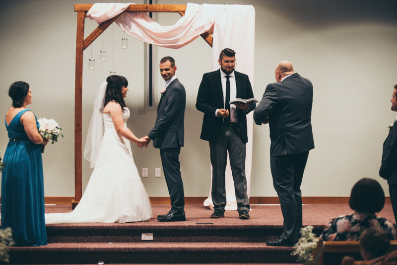 groomsman giving rings to the pastor