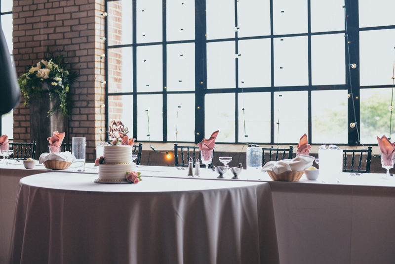 head table decorated with pink napkins and flowers