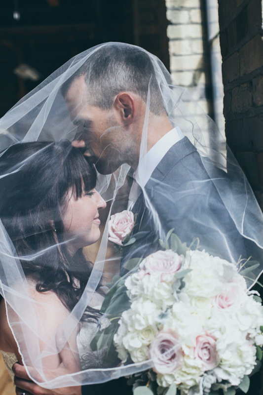 bride and groom under the veil, he is kissing her forehead