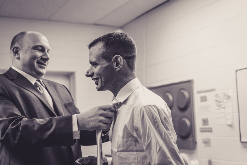 black and white image of groomsman helping groom with tie
