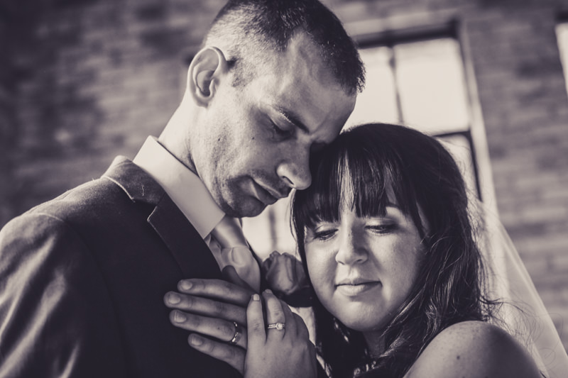black and white image of a bride and groom in a room with brick walls