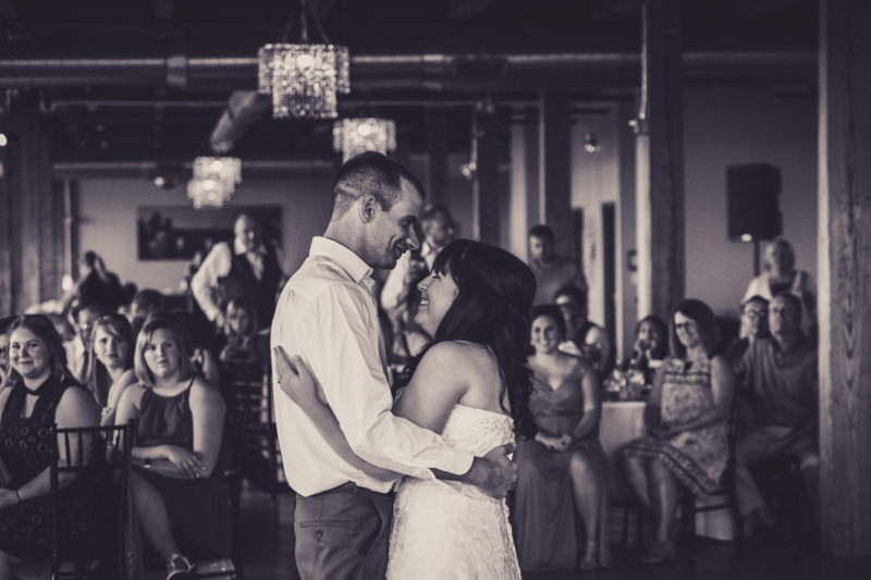 black and white image of a bride and groom dancing in a city view wedding venue