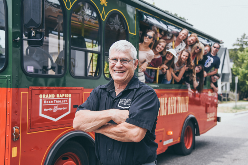 gray haired trolley driver standing in front of a red trolley with clients laughing out the windows