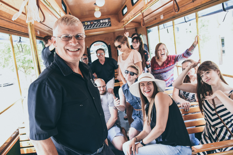 driver taking photo with guests on an open air trolley
