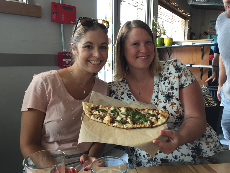 two ladies holding up a pan of pesto breadsticks at brewing company