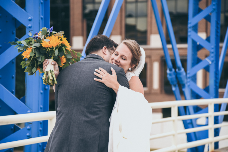 bride and groom on a blue bridge during first look before ceremony