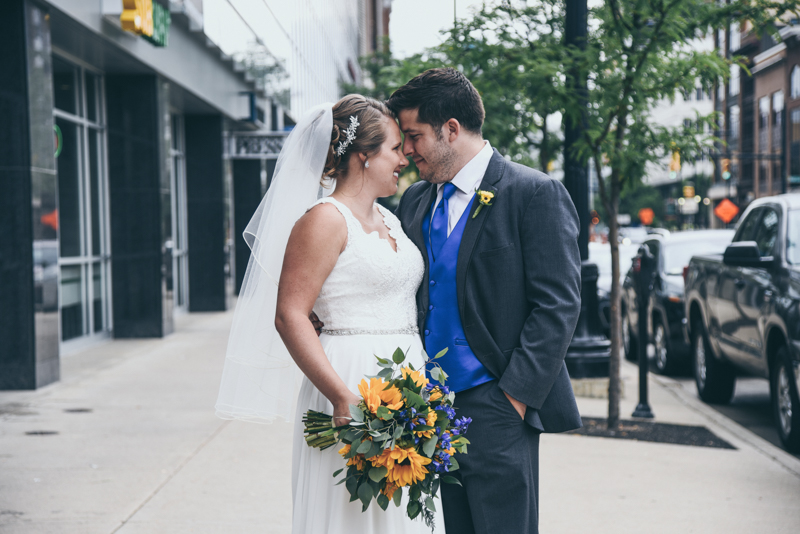 bride and groom taking photos together on a downtown street
