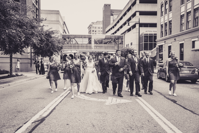 black and white image of a bridal party walking in a downtown street