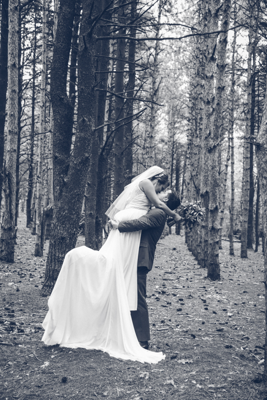 bride and groom taking photos in a pine forest