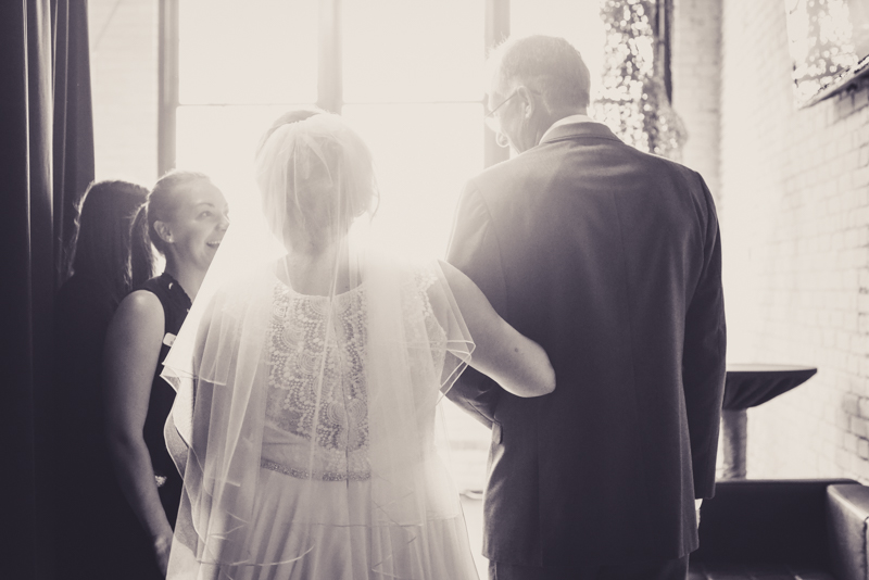 black and white image of a father walking a daughter down the aisle