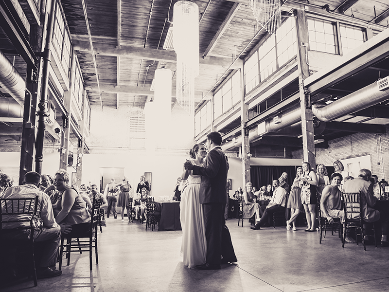 bride and groom dancing in a loft venue