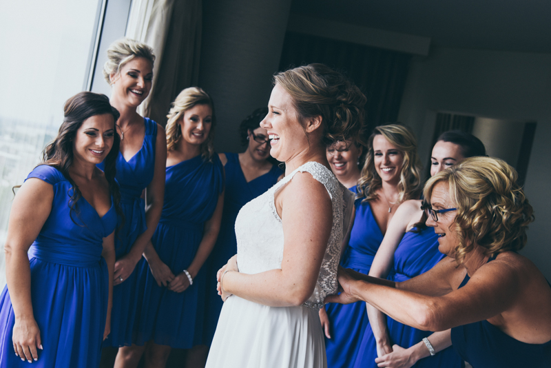 bride and her bridesmaids laughing together in a hotel room as they get ready
