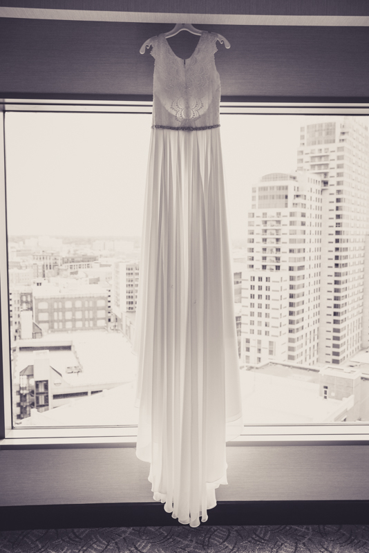 black and white photo of a wedding dress hanging in a hotel window