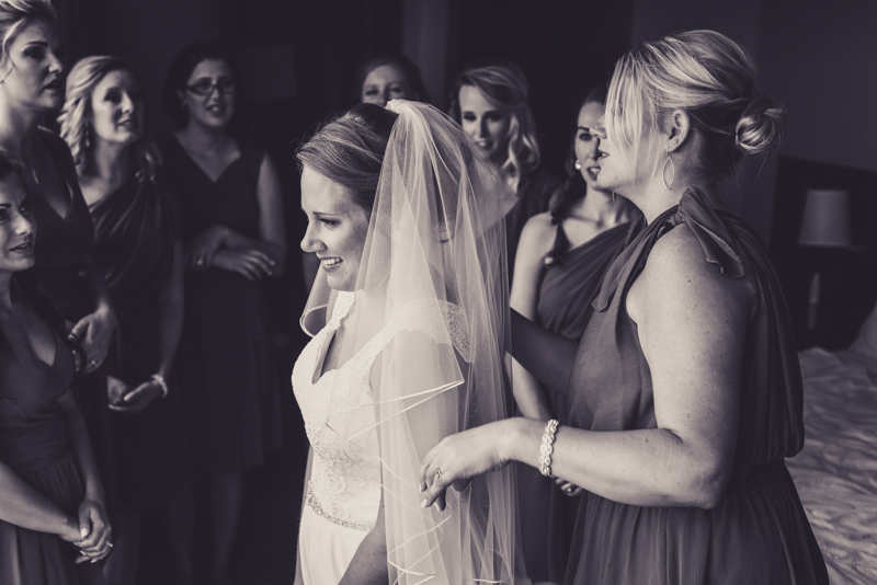 black and white image of a bride getting her veil put on while the bridesmaids watch