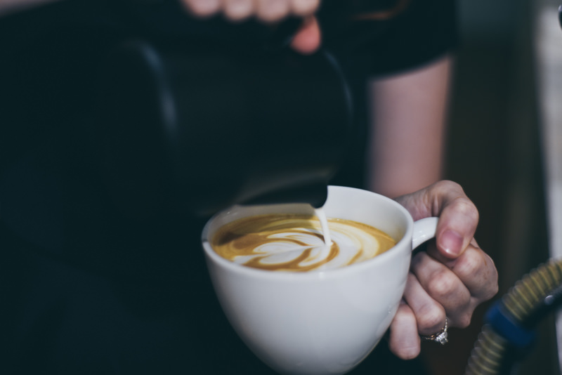 barista pouring a latte