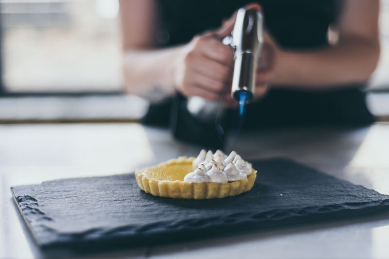 a pastry chef caramelizing a dessert