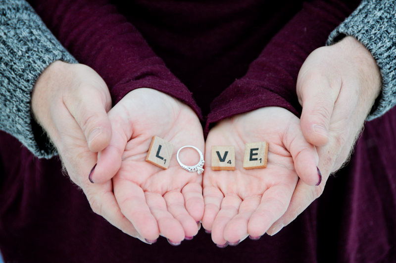 man and woman's hands holding scrabble pieces that spell love with a ring for the l