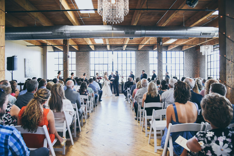 large wide shot of wedding ceremony in an old city view loft brick building
