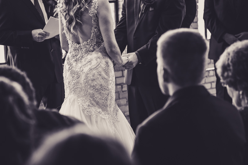 black and white image of a bride and groom holding each others hands