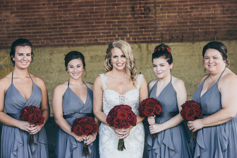 bride and bridesmaids in gray with rich red bouquets
