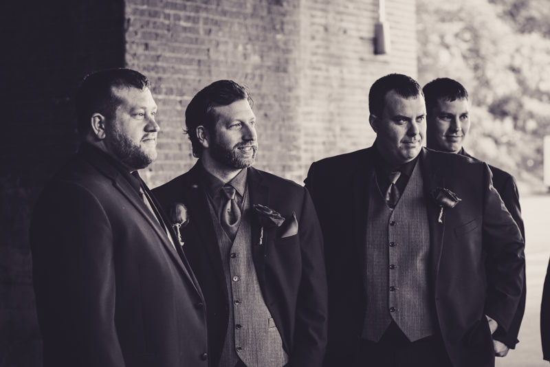groom and groomsmen in black tuxes with gray vests and red rose boutonnieres