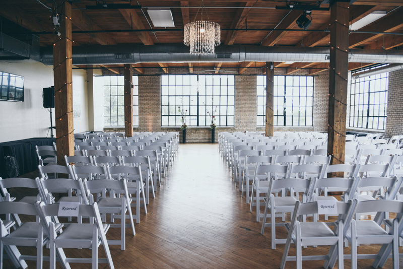 beautiful white chairs set up for a wedding ceremony in a city view loft venue