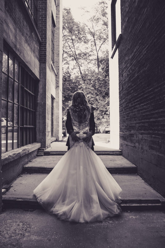 black and white image of bride and groom together in an alleyway holding each other