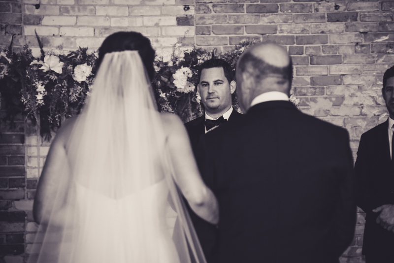 grooms face as his bride walks down the aisle
