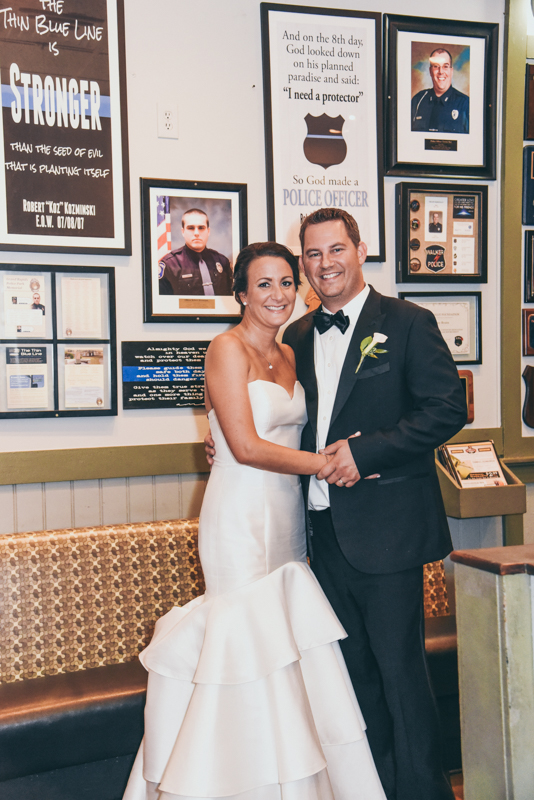 bride and groom in front of a wall for fallen heroes