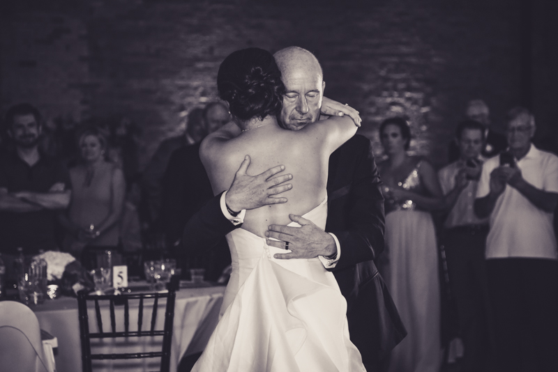bride and groom dancing with friends and family at reception