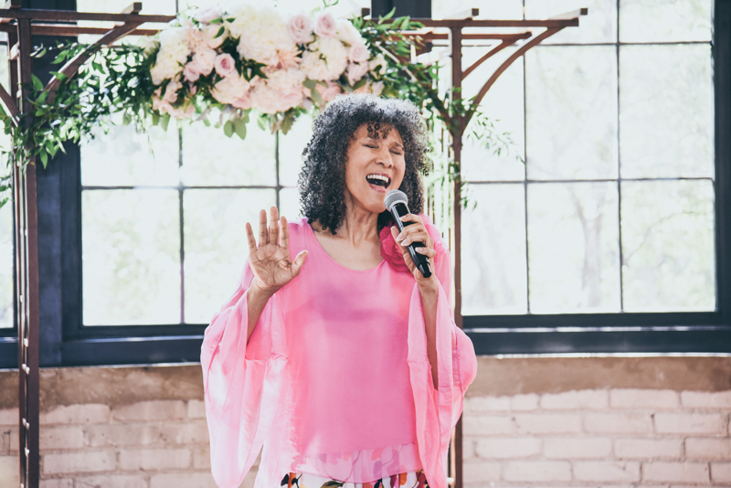 soloist in a pink shirt at a wedding