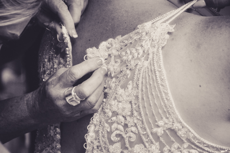 detailed close up shot of the back of a brides dress being fastened