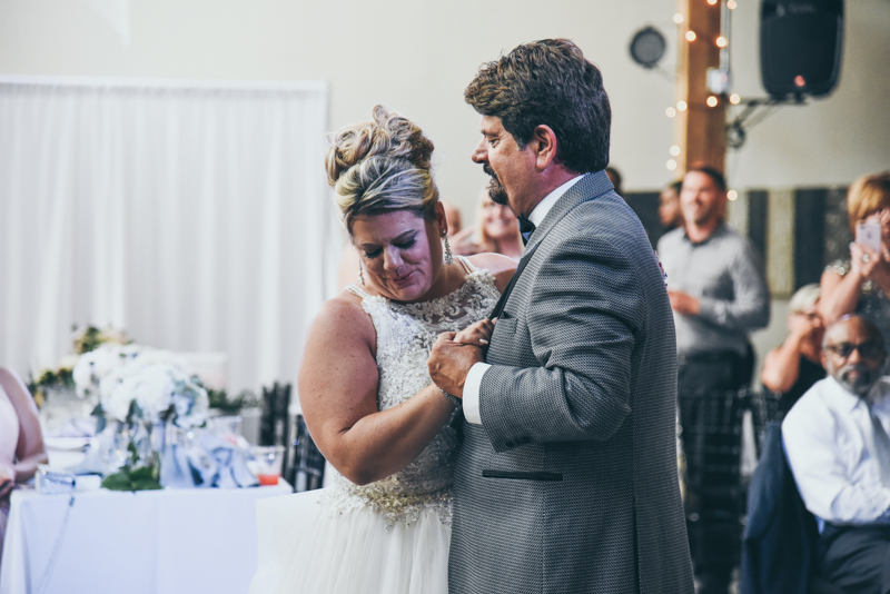 father daughter dance while a video plays in the background