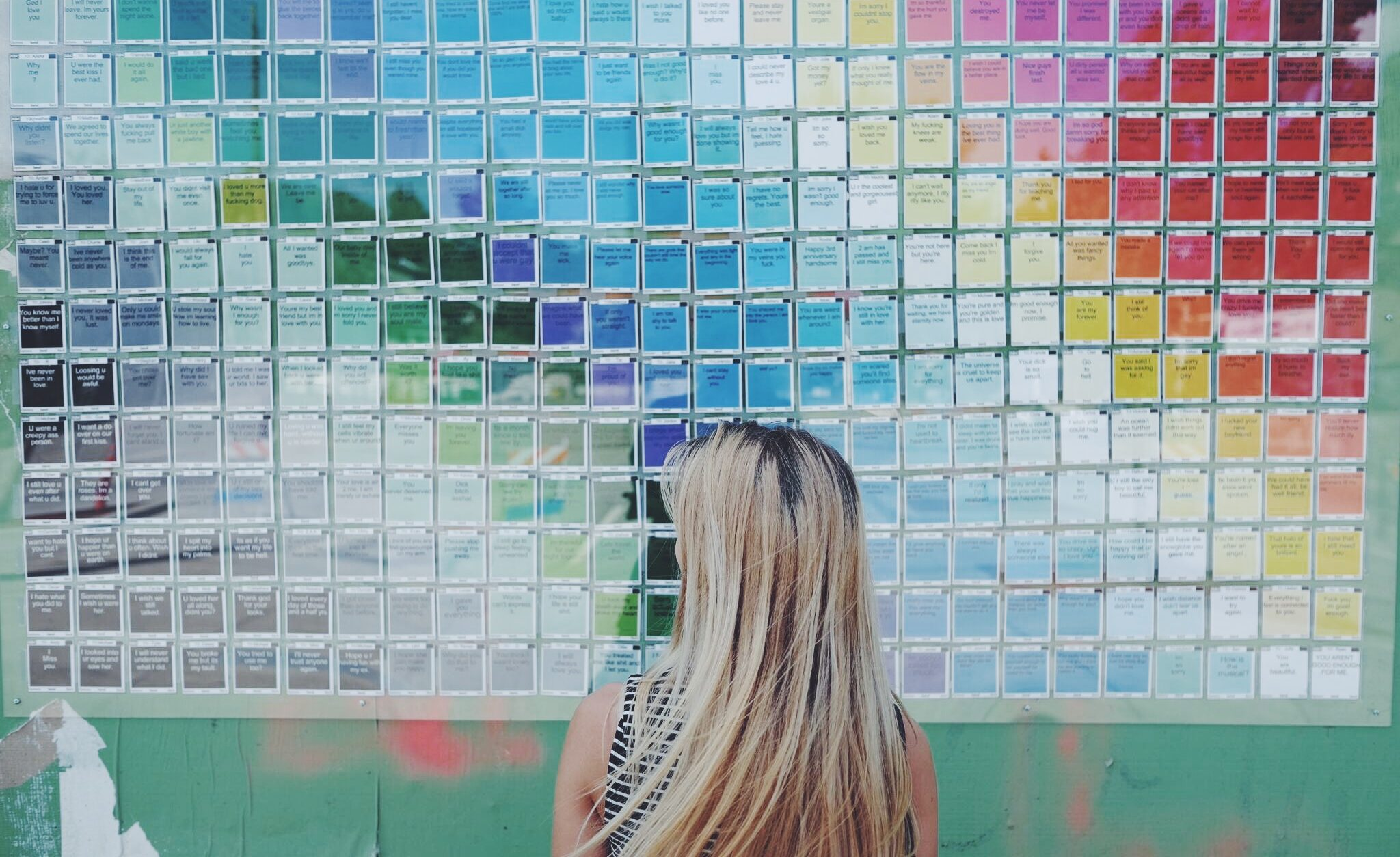 artist looking at installed art piece with colorful tiles