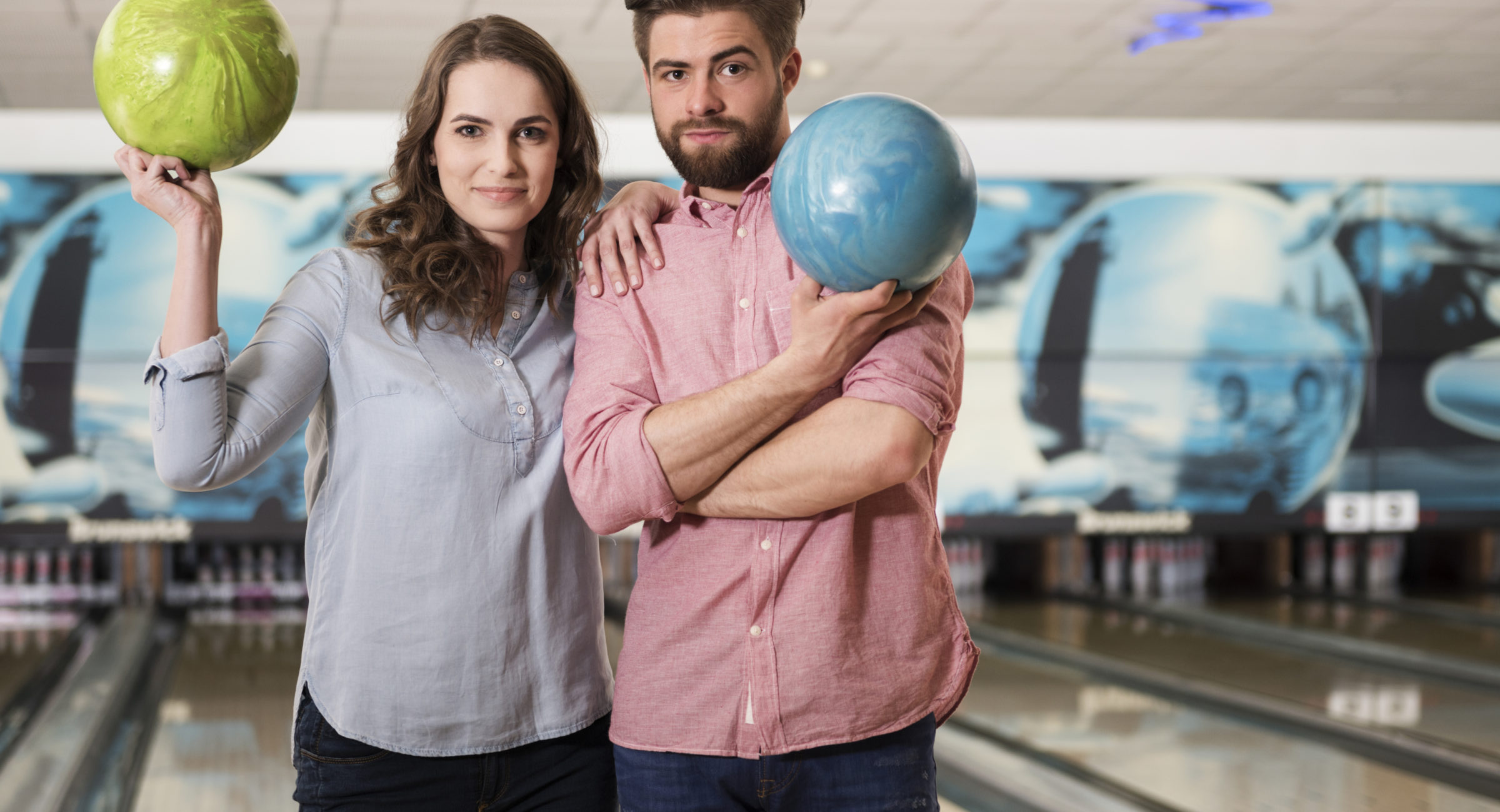 man and woman holding bowling balls at the lanes