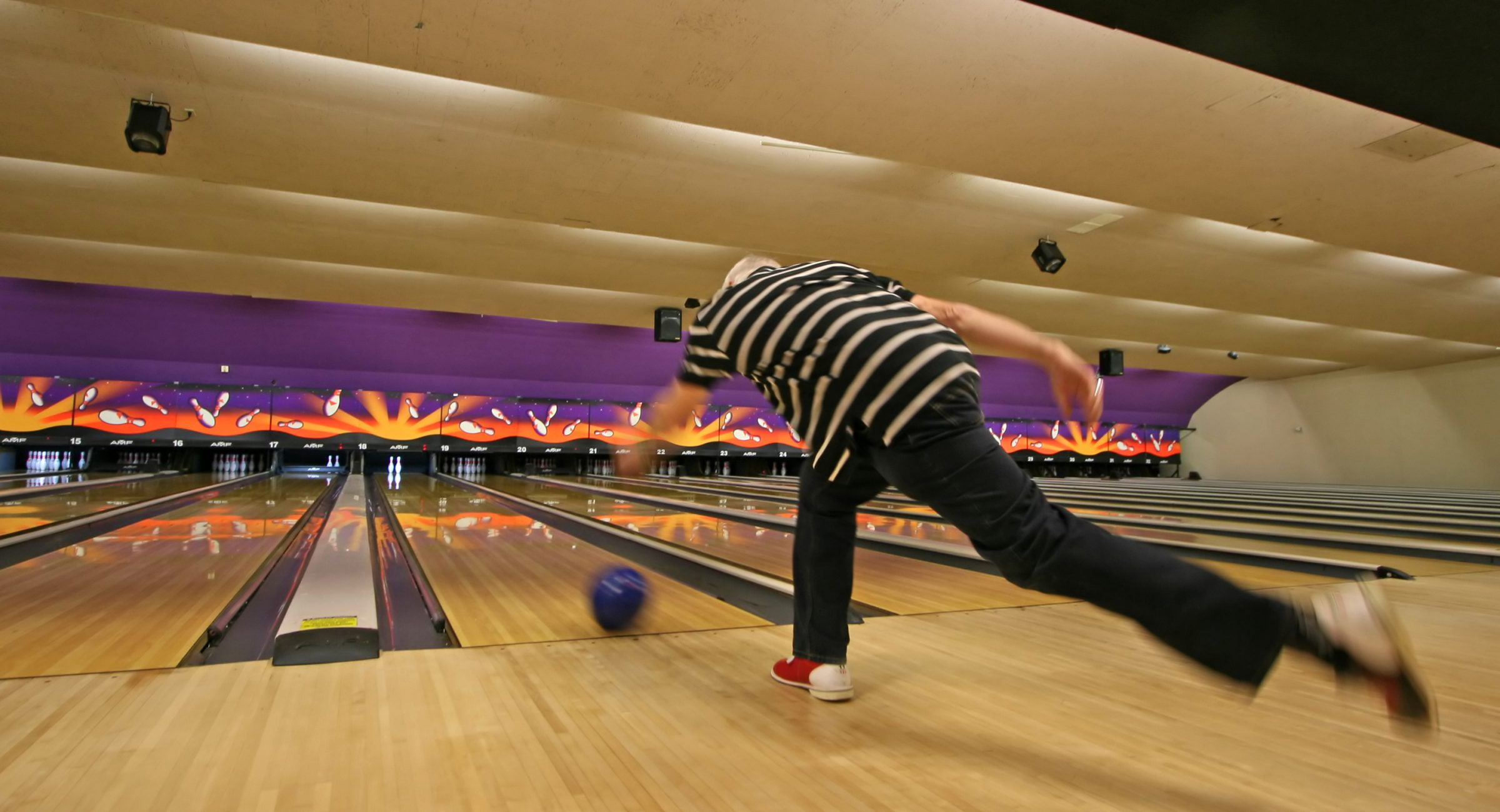 A man who has just thrown his bowling ball