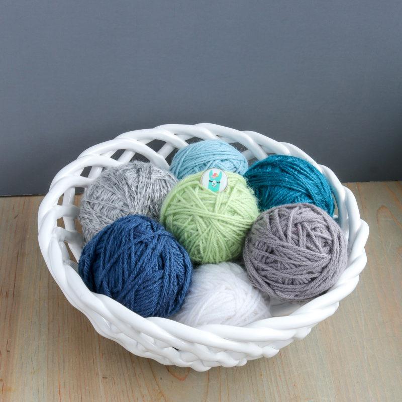Several balls of yarn displayed in a ceramic bowl