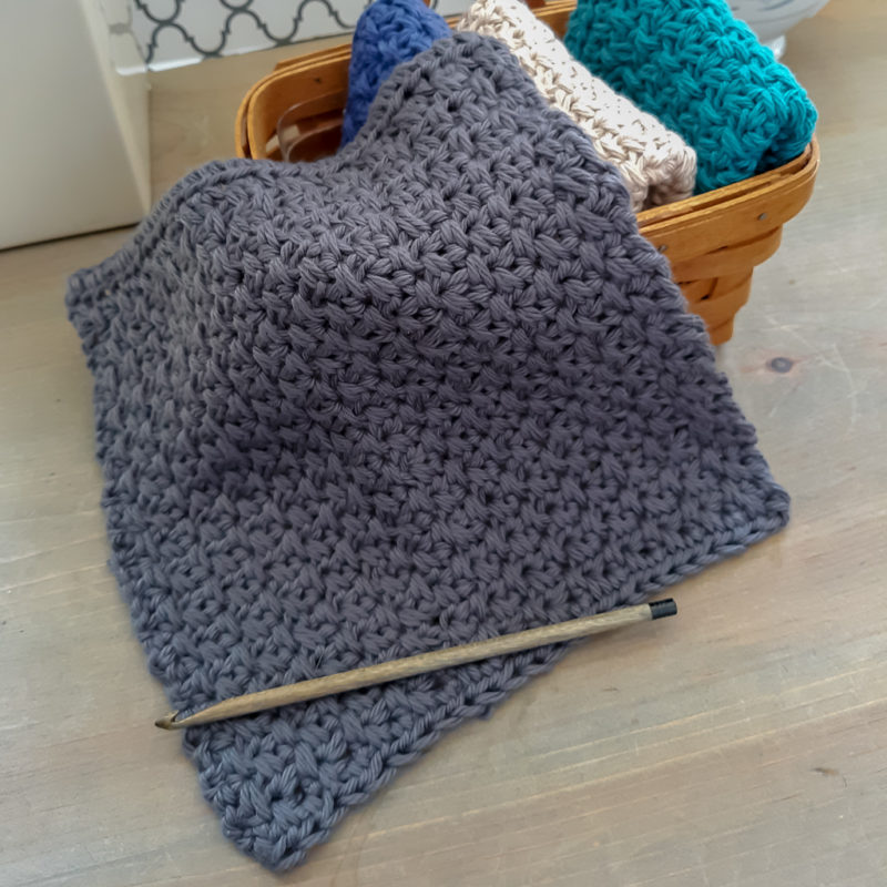 Flat lay of crochet dishcloth with wood crochet hook