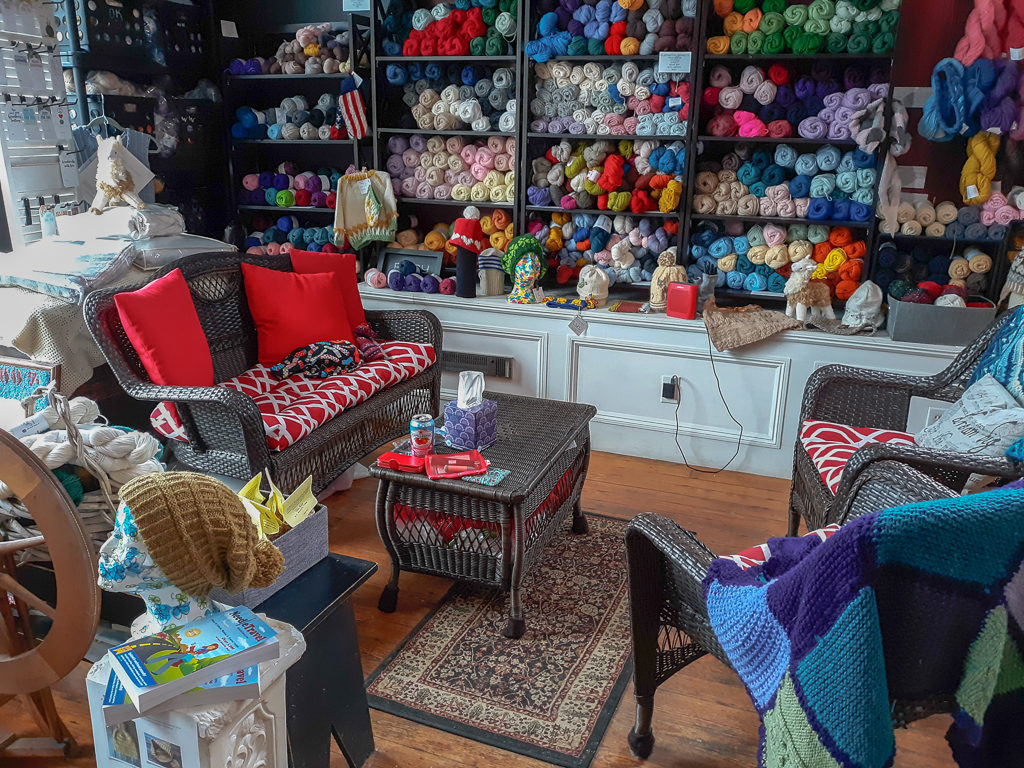 Image of couch, coffee table, and chairs surrounded by yarn