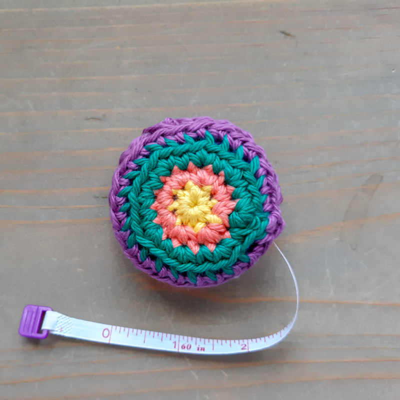 Crochet Tape Measure with 3 inches of tape out on neutral wood backgound