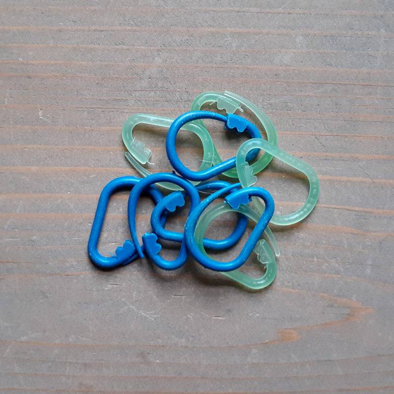 Plastic crochet stitch markers on a wood neutral background