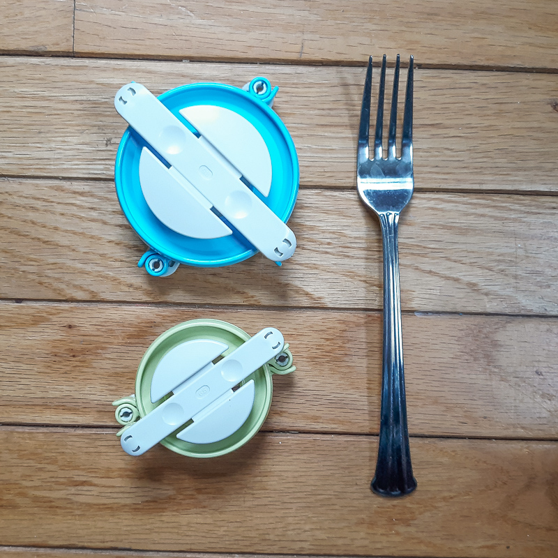 Flat lay of large and small pom pom maker and a dinner fork