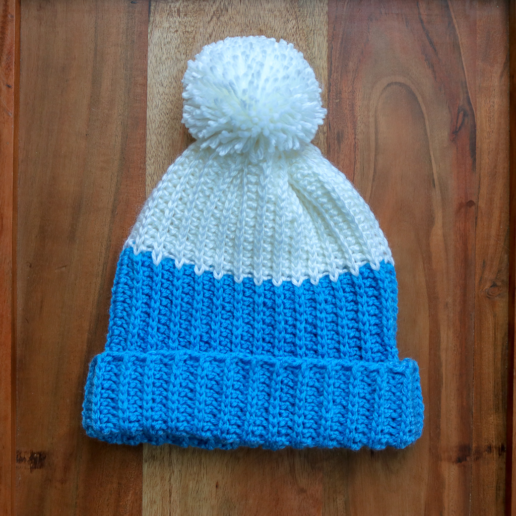 Flat lay of Modern Pompom hat on wood background