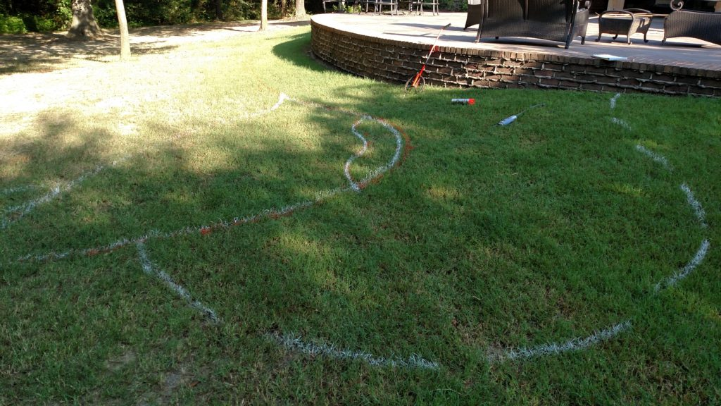 drawing out the pool design using spray paint in the grass