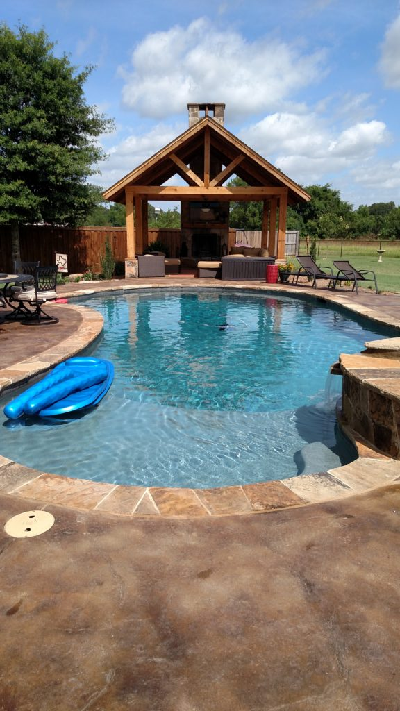pool with outdoor kitchen under pergola