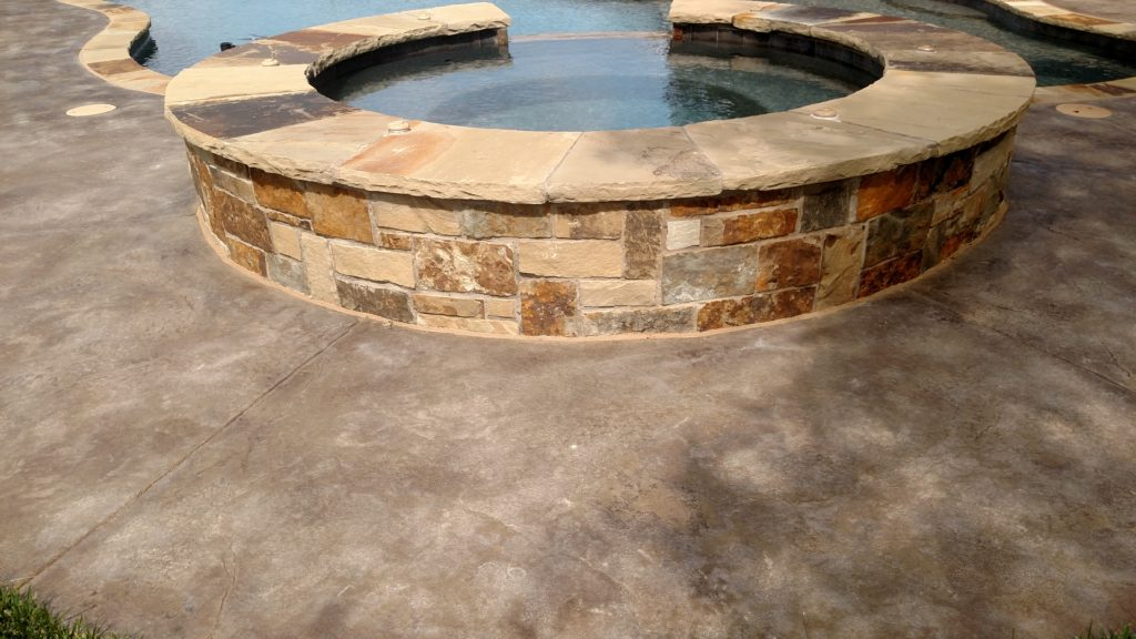 raised spa with stamped concrete and flagstone coping