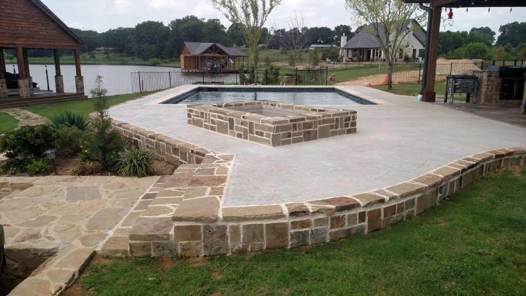 stamped concrete deck with fire pit by pool